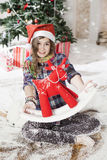 Beautiful young woman in a Santa hat sitting on the floor near C Stock Photography