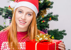 Beautiful young woman with Santa hat smiling holding a big Christmas present. Stock Photos