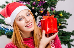 Beautiful young woman with Santa hat smiling holding a Christmas present. Stock Image