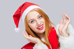 Beautiful young woman with Santa hat smiling looking happy surprised. Portrait of a Christmas girl with red hat and winter scarf. Merry Christmas Stock Photography