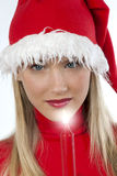 Beautiful young woman in santa's hat holding a. Red candle Royalty Free Stock Photos