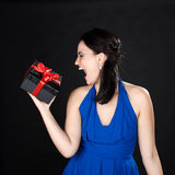 Beautiful young woman screaming at gift box Royalty Free Stock Photography