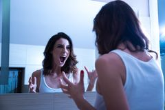 A beautiful young woman screaming. In the mirror in the bathroom Stock Image