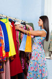 Beautiful young woman searches clothes in a row Stock Photography