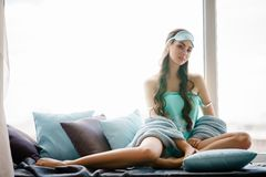Beautiful Young Woman Seating At Window Pillows In Turquoise Pajama Set Stock Images
