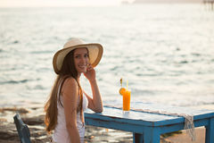 Beautiful young woman seating in cafe by seaside with orange jui. Beautiful and fit young woman with long straight hair wearing white t-shirt and hat smiling and Royalty Free Stock Image