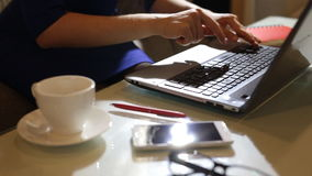 Beautiful young woman is seating indoors at a cafe restaurant, holding a coffee cup while using her laptop pc. Young woman is seating indoors at a cafe stock video