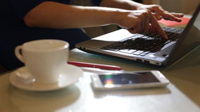 Beautiful young woman is seating indoors at a cafe restaurant, holding a coffee cup while using her laptop pc stock footage