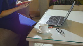 Beautiful young woman is seating indoors at a cafe restaurant, holding a coffee cup while using her laptop pc stock video footage