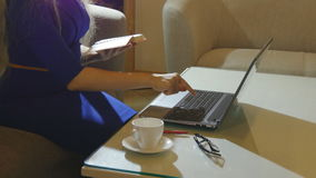 Beautiful young woman is seating indoors at a cafe restaurant, holding a coffee cup while using her laptop pc. Young woman is seating indoors at a cafe stock video footage