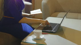 Beautiful young woman is seating indoors at a cafe restaurant, holding a coffee cup while using her laptop pc. Young woman is seating indoors at a cafe stock footage