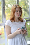 Beautiful Young Woman Sees Something Disturbing on the Phone. Head shot of a very attractive young woman with red hair and stunning blue eyes. She  wearing a a Stock Photography
