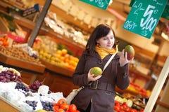 Beautiful young woman selecting mangoes Royalty Free Stock Photo