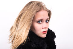 Beautiful young woman in semi profile. With a black fur jacket with a white background behind Royalty Free Stock Photography