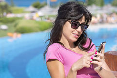 Beautiful young woman sending sms. Beautiful young surprised woman  receiving  sms on a pool background Royalty Free Stock Image