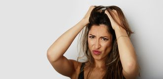 Beautiful young woman with a severe headache with the hands in the head over white empty wall on background. Beauty and. Healthcare concept.Wide stock image