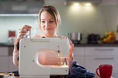 Beautiful young woman sewing clothes with sewing machine Royalty Free Stock Photos
