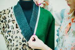 Beautiful young woman sews designer coat. Leopard print coat and green. royalty free stock photography