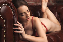 Beautiful young woman in red underwear laying on leather so Royalty Free Stock Photography