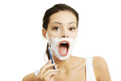 Beautiful young woman shaving her face Stock Photo