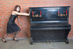 Beautiful young woman shifts heavy-weight piano Royalty Free Stock Images