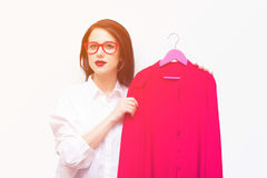 Beautiful young woman with shirt on hanger standing in front of Royalty Free Stock Photo