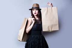 Beautiful young woman with shoping bags standing in front of won. Beautiful young woman with shopping bags standing in front of wonderful white studio background royalty free stock photography