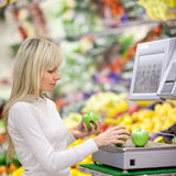 Beautiful young woman shopping. For fruits and vegetables in produce departmant of a grocery store/supermarket (shallow DOF Royalty Free Stock Image