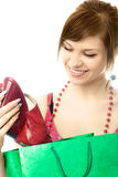 Beautiful young woman with a shopping bag. Looking at the shoes she has just bought Stock Photos