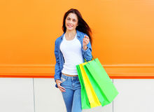 Beautiful young woman with shopping bags in jeans clothes. Over orange wall Stock Photography