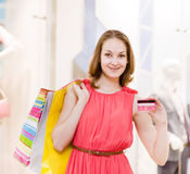 Beautiful young woman with shopping bags showing credit card Royalty Free Stock Photography