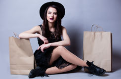 Beautiful young woman with shopping bags sitting in front of won. Derful white studio background Royalty Free Stock Images