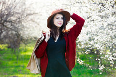 Beautiful young woman with shopping bags standing in front of wo Stock Photography