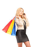 Beautiful young woman with shopping bags talking on a phone Stock Photo