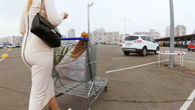 Beautiful young woman with shopping cart going to the car stock footage
