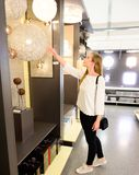 Beautiful young woman shopping chandelier lights fro her home.  stock photography