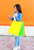 Beautiful young woman with shopping colorful bags in jeans Stock Photography