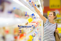 Beautiful young woman shopping for diary products at a grocery Royalty Free Stock Photos