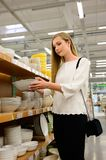 Beautiful young woman shopping dishes for her new home stock photography
