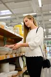 Beautiful young woman shopping dishes for her new home royalty free stock image