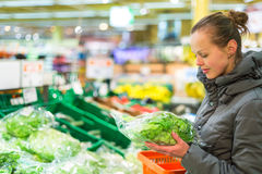 Beautiful, young woman shopping for fruits and vegetables in pro Royalty Free Stock Images