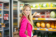 Beautiful young woman shopping for fruits and vegetables Stock Image