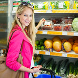 Beautiful young woman shopping for fruits and vegetables Royalty Free Stock Images