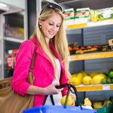 Beautiful young woman shopping for fruits and vegetables Royalty Free Stock Photo