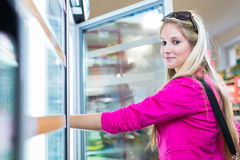 Beautiful young woman shopping in a grocery store/supermarket. (color toned image Stock Photography