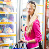 Beautiful young woman shopping in a grocery store/supermarket Stock Images