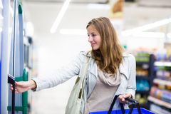 Beautiful young woman shopping in a grocery store Royalty Free Stock Image