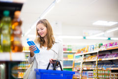 Beautiful young woman shopping in a grocery store Stock Photos