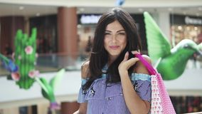 Closeup portrait of happy girl with gift bags. Young woman with shopping bags in hands. 20s. Beautiful young woman in shopping mall doing her shopping stock video footage