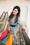 Beautiful young woman shopping in mall. Holding shopping bags standing on escalator Royalty Free Stock Photo